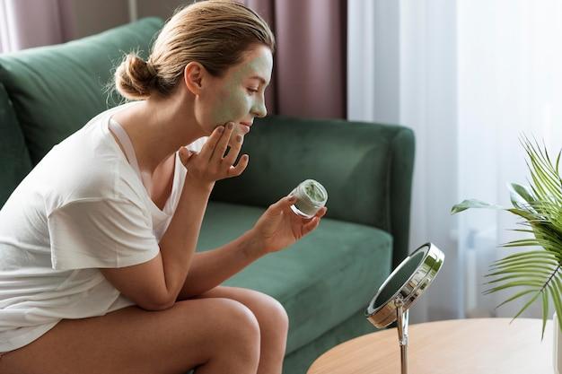 Женщина, применяя маску для лица в зеркале