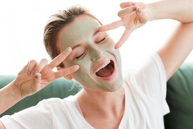 顔のマスクとピースサインのジェスチャーを持つ女性