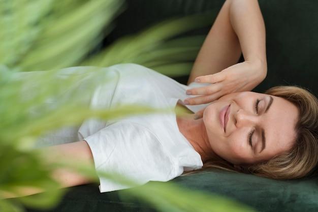 Женщина отдыхает на диване и размытым растением
