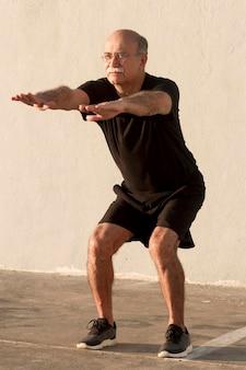 Человек делает фитнес приседания на свежем воздухе