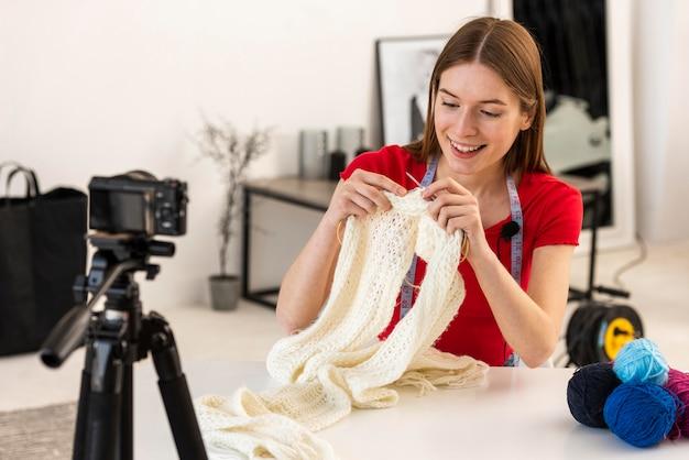 ファンのためにカメラで編み物をする若いブロガー