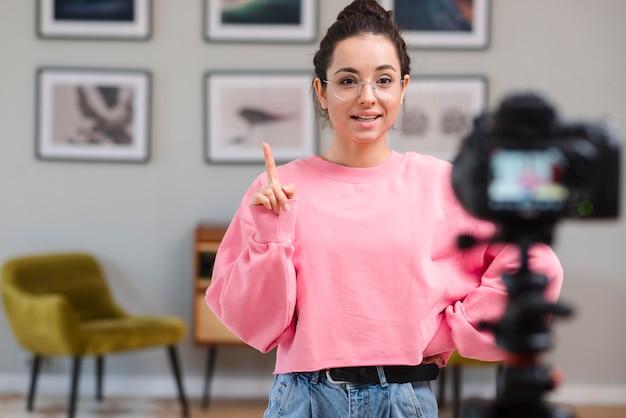Молодая женщина записывает видео у себя дома