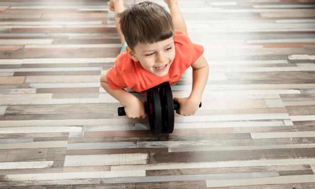 Прелестный мальчик тренируется из дома