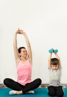 Прелестный мальчик тренируется вместе с матерью