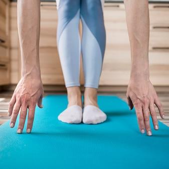 Макро женщина растяжения на коврик для йоги