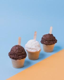 Чашка с ванильным и шоколадным мороженым на столе