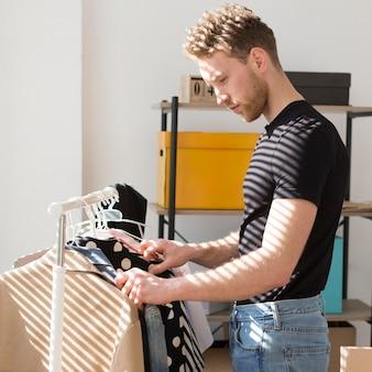 Мужчина среднего роста смотрит на одежду