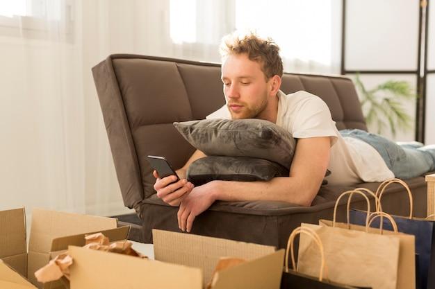 スマートフォンを保持しているソファの上の男