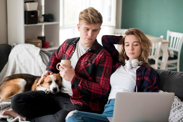 Пара с собакой смотрит на ноутбук