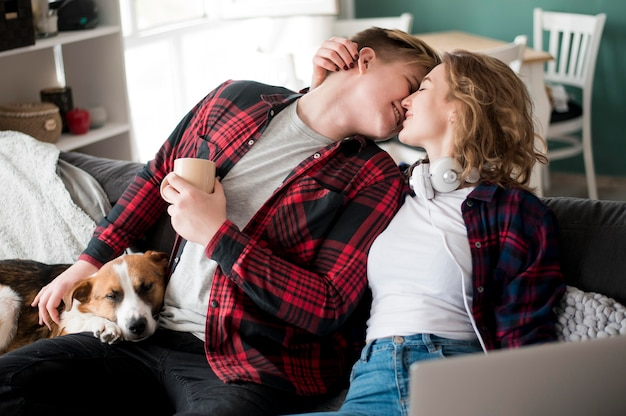 カップルが犬の横にキス