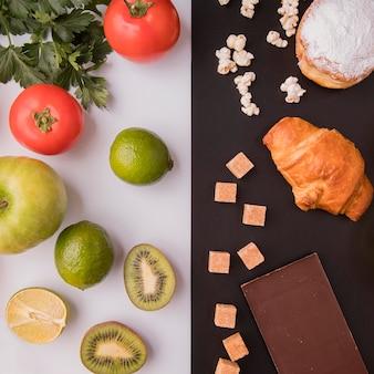 Вид сверху на фрукты и овощи против нездоровых сладостей