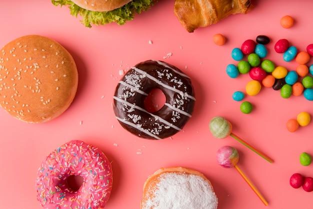 Вид сверху пончики, гамбургеры и сладости