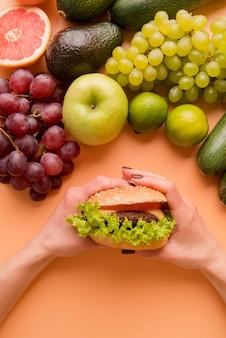 Вид сверху рука гамбургер возле фруктов