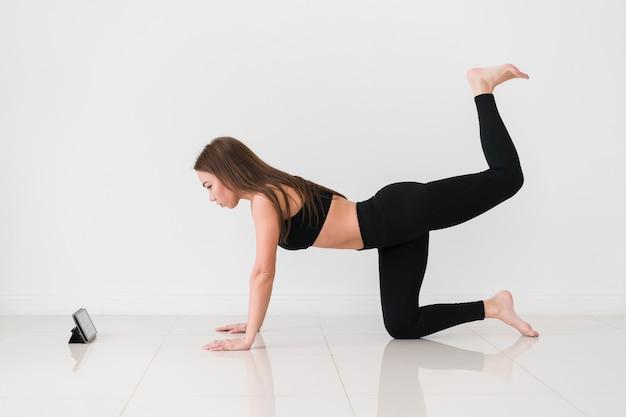 Женщина делает упражнения фитнес с мобильного телефона