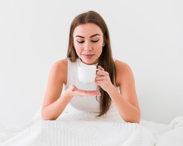 Милая девушка пьет кофе в постели