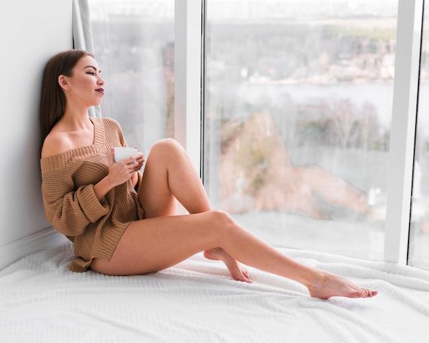 Длинный вид женщина сидит рядом с окнами