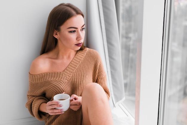 Женщина сидит рядом с окнами и пьет кофе