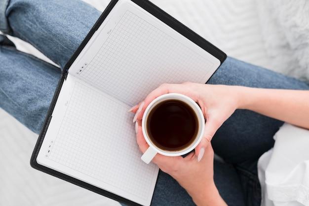 Вид сверху женщина держит чашку кофе