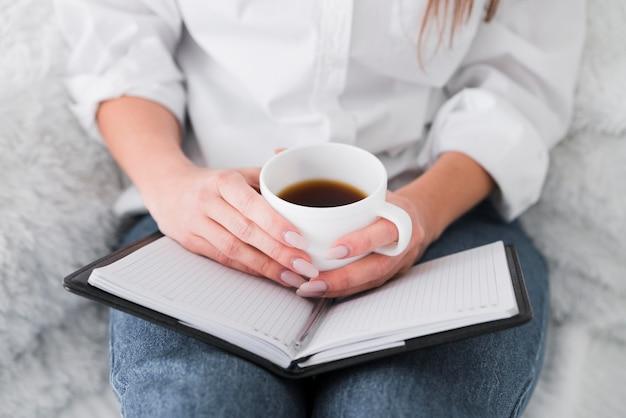 Женщина вид спереди держит чашку кофе