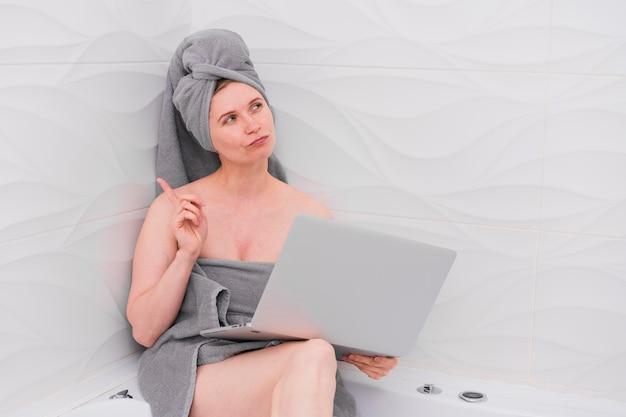 Женщина держит ноутбук в ванной комнате