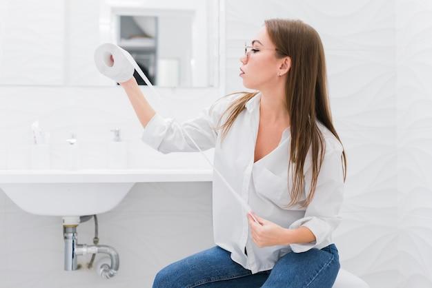 トイレに座りながらトイレットペーパーを探している女性