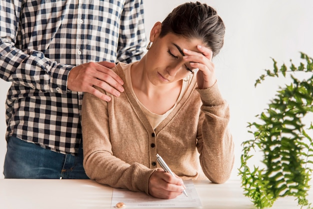 悲しい女性が離婚協定に署名