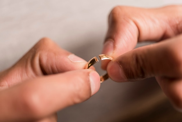 Макро руки держат сломанное кольцо