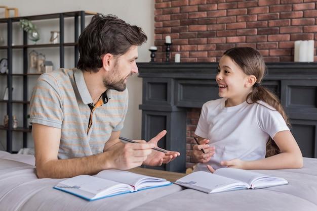 サイドビューのお父さんが女の子に書くことを教える