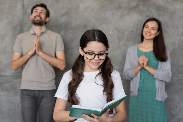 読んでいる女の子に耳を傾ける親