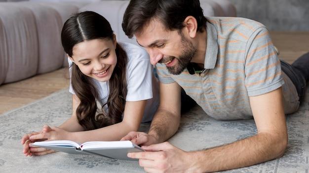 Улыбающийся отец и дочь читают