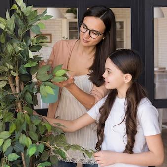 Мама и девочка ухаживают за растениями