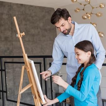 Отец учит девочку рисовать