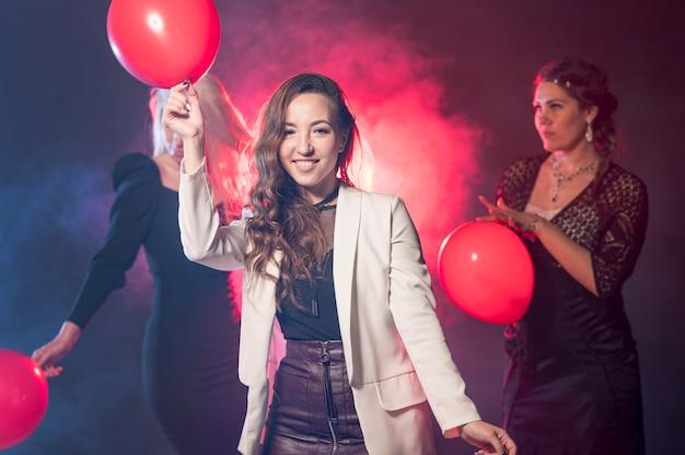 パーティーで風船を持つ若い女性