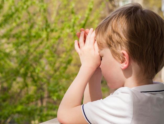 Вид сбоку маленького мальчика молиться