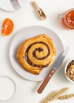 Вид сверху вкусного булочки с корицей на столе
