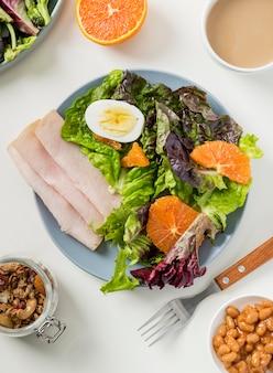 Вид сверху здоровый завтрак с салатом и ветчиной