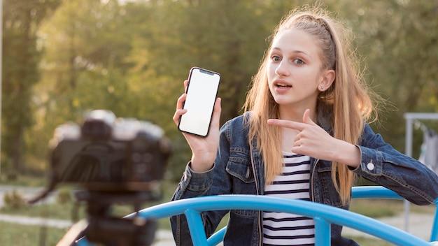 Средний снимок девушка держит смартфон