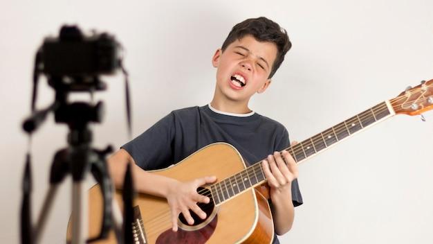 Малышка среднего размера играет на гитаре
