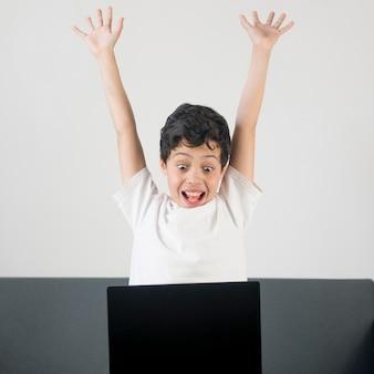 ラップトップで正面興奮少年