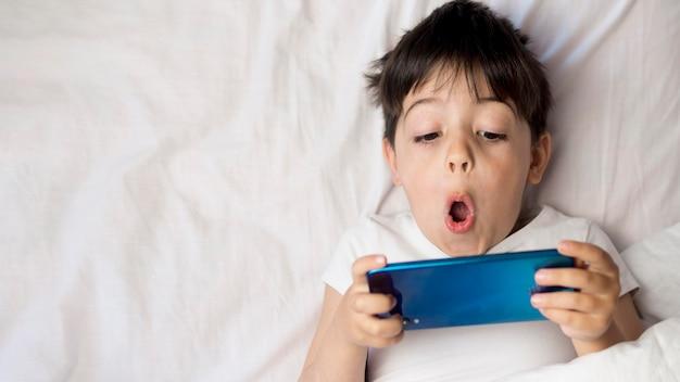 Плоский лежал ребенок с телефоном в постели