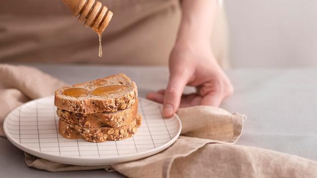 Крупным планом мед на ломтики хлеба
