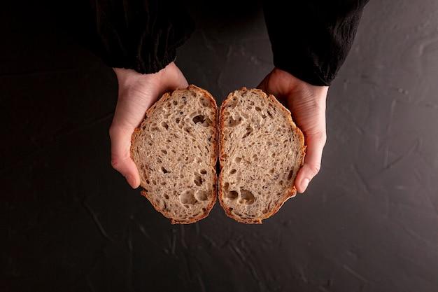 Руки крупного плана держа взгляд сверху хлеба
