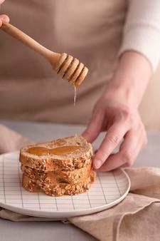 クローズアップ手パンに蜂蜜を注ぐ