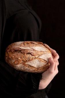 Макро руки держат хлеб вид сбоку