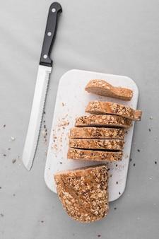 Вид сверху нарезанный хлеб с ножом