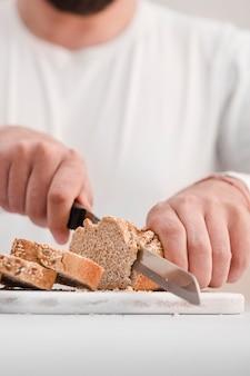 クローズアップ男がパンを切る