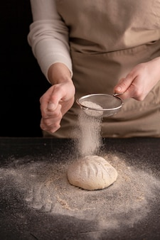 Макро руки, делая хлеб с мукой