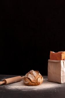 Маленький хлеб на темном столе
