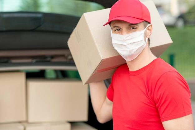 Парень доставки в маске держит коробку