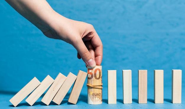 紙幣と倒れた木片を保持している女性